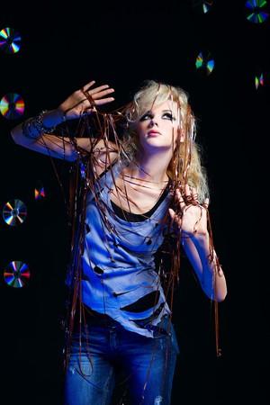 potrait of beautiful blonde girl glam rocker gets entangled in audio tape. multiple shiny cds on dark background. photo