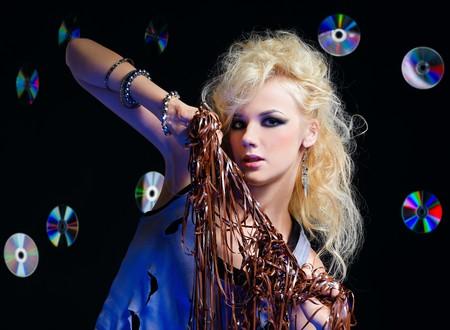 potrait of beautiful blonde girl glam rocker gets entangled in audio tape. multiple shiny cds on dark background.