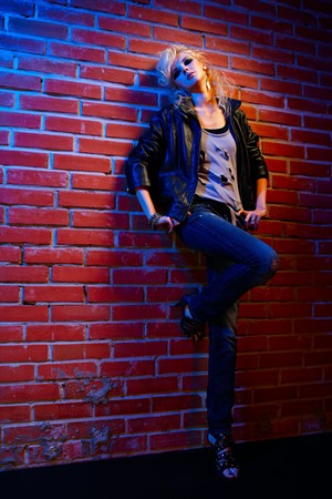 glam: full-length portrait of beautiful glam rock style blonde girl standing near red brick wall on one leg