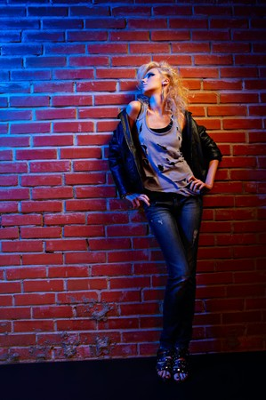 glam: full-length portrait of beautiful glam rock style blonde girl standing near red brick wall