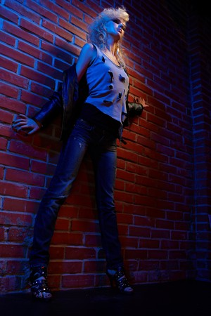 wide angle full-length portrait of beautiful glam rock style blonde girl standing near red brick wall photo