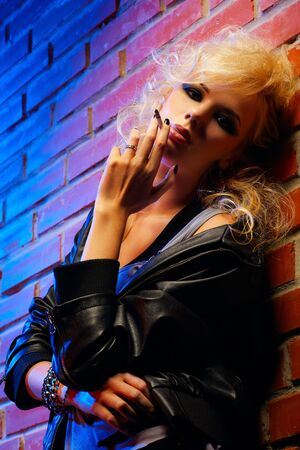 glam: portrait of beautiful blonde girl in torned tank top and leather jacket smokin cigarette near red brick wall