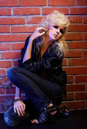 portrait of beautiful glam rock style blonde girl sitting near red brick wall photo