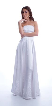 estimating: beatiful young woman in wedding dress on white looks estimating something with a hand near her hand