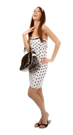 beautiful cheerful model poses in polka-dot dress with black bag on white Stock Photo - 8147139