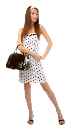 beautiful cheerful model poses in polka-dot dress with black bag on white Stock Photo - 8147162