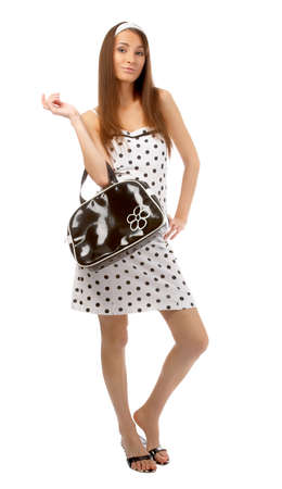 beautiful cheerful model poses in polka-dot dress with black bag on white Stock Photo - 8147174