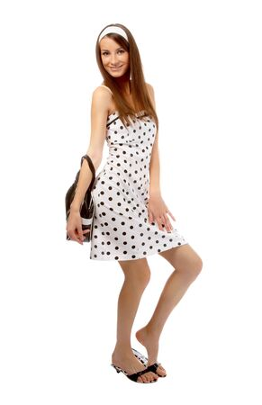 beautiful cheerful model poses in polka-dot dress with black bag on white Stock Photo - 8147171