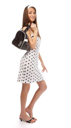 beautiful cheerful model poses in polka-dot dress with black bag on white Stock Photo - 8147192