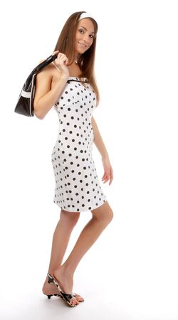 beautiful cheerful model poses in polka-dot dress with black bag on white Stock Photo - 8147233