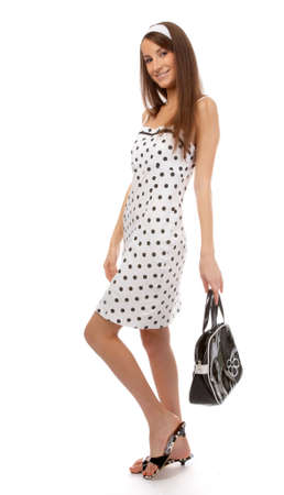 beautiful cheerful model poses in polka-dot dress with black bag on white Stock Photo - 8147235