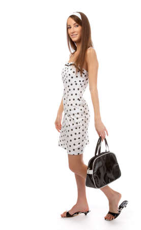 beautiful cheerful model poses in polka-dot dress with black bag on white Stock Photo - 8147317