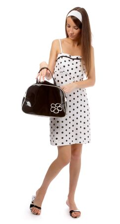 beautiful cheerful model in polka-dot dress is trying to find something in her black bag Stock Photo - 8147236