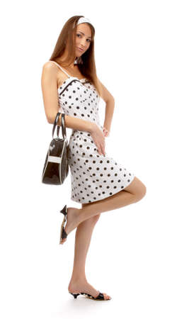 beautiful cheerful model poses on one leg in polka-dot dress with black bag on white Stock Photo - 8147178