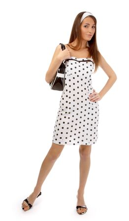 beautiful cheerful model poses in polka-dot dress with black bag on white Stock Photo - 8147194