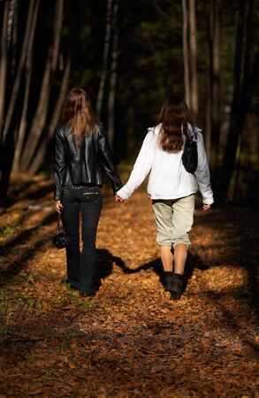 Girls walking along the path in the autumnal forest  photo