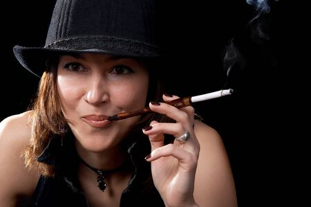 Woman in hat with cigarette holder isolated on the black background photo