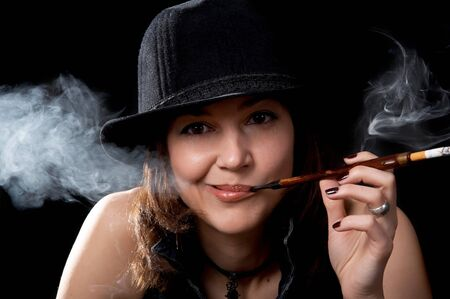 Woman in hat with cigarette holder isolated on the black background Stock Photo - 8216164