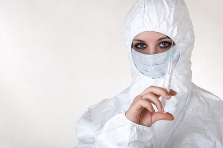 Doctor in white coat and mask with syringe