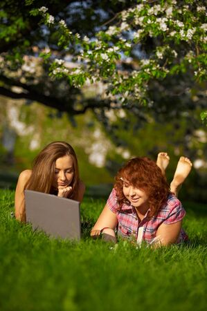 two student girls studying outdoors on grass Stock Photo - 8216279