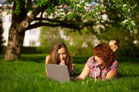 two student girls studying outdoors on grass photo