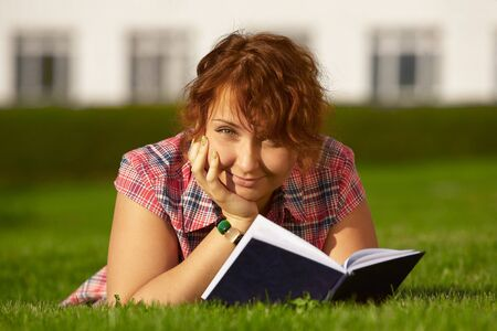 two female students studying outdoors on grass photo