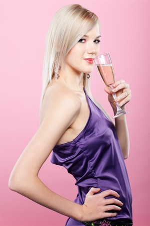 gala: portrait of beautiful blonde party girl with glass of champagne on pink Stock Photo
