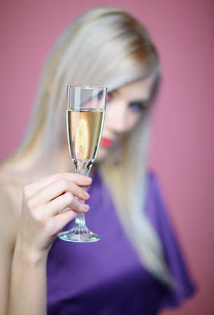 Low depth of field image -  beautiful blonde woman with glass of champagne on pink photo