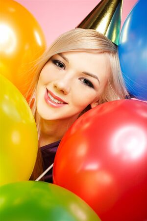 close-up portrait of beautiful blonde party girl with balloons on pink photo
