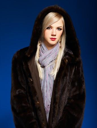 portrait of beautiful european blonde girl in fur coat on blue Stock Photo - 8216434
