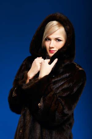 portrait of beautiful european blonde girl in fur coat on blue photo