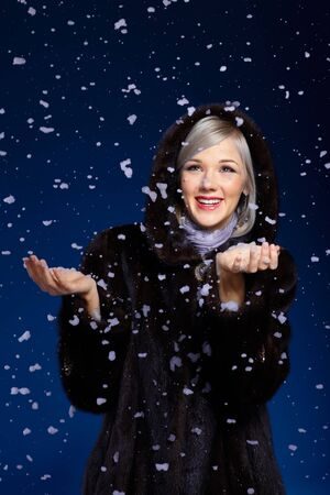 beautiful european blonde woman in fur coat smiling in snow flakes on blue photo