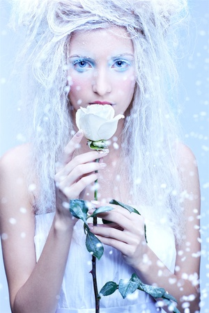 nymphs: close-up portrait of beautiful blonde frozen fairy nymph girl with white rose Stock Photo