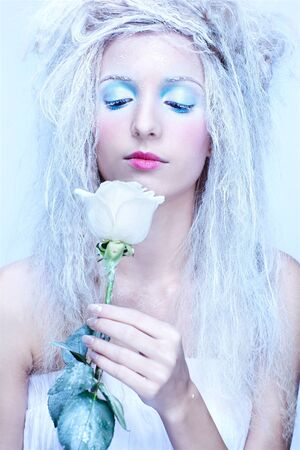 close-up portrait of beautiful blonde frozen fairy nymph girl with white rose photo