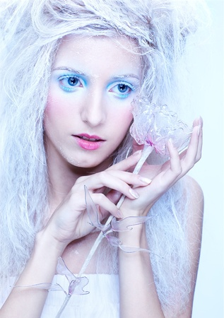 portrait of beautiful blonde frozen fairy girl with glass rose photo
