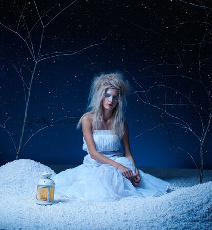 portrait of beautiful frozen fairy nymph girl sitting on snow with lamp photo