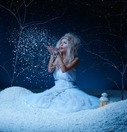 nymph: portrait of beautiful frozen fairy nymph girl sitting on snow and blowing snowflakes from her hands Stock Photo