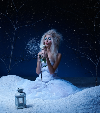 blow: portrait of beautiful winter fairy nymph girl sitting on snow and blowing off snowflakes from frozen rose