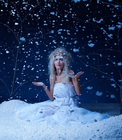 portrait of beautiful frozen fairy nymph girl sitting in snowfall photo