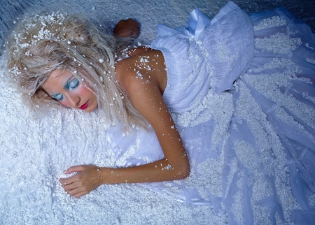 portrait of beautiful frozen fairy nymph girl sleeping on snow photo