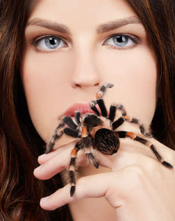 close-up brachypelma smithi spider sitting on girls hand and stretching out to her mouth photo