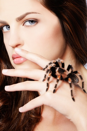 close-up portrait of girl with brachypelma smithi spider creeping over her hand photo