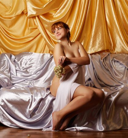 portrait of beautiful redhead girl with bunch of grapes sitting on sofa covered with silver cloth. photo