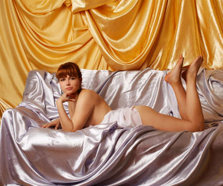 portrait of beautiful redhead girl on sofa covered with silver cloth. golden cloth on background photo