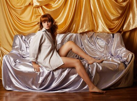 portrait of beautiful redhead girl in shirt sitting on sofa covered with silver cloth. golden cloth on background photo