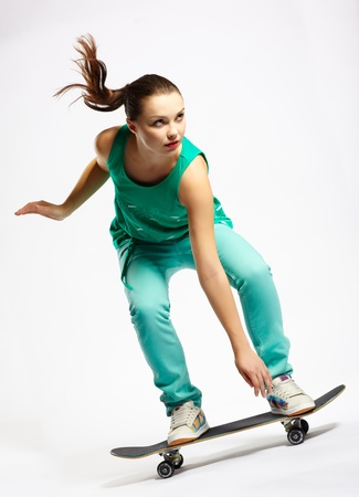 Skateboarder girl skating on skateboard with high speed photo