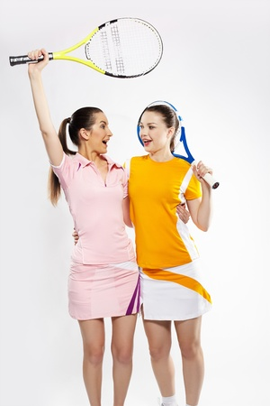 portrait of two sporty girls tennis players with rackets photo