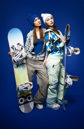 portrait of two beautiful sporty girls with snowboards on blue photo