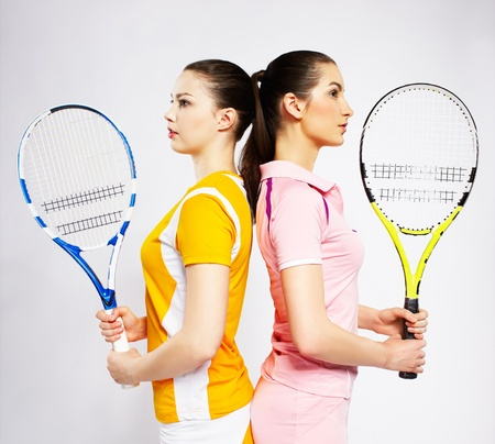 portrait of two sporty girls tennis players with rackets standing back to back photo
