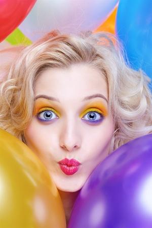 beso: Retrato de una hermosa chica rubia con globos de cumpleaños Foto de archivo